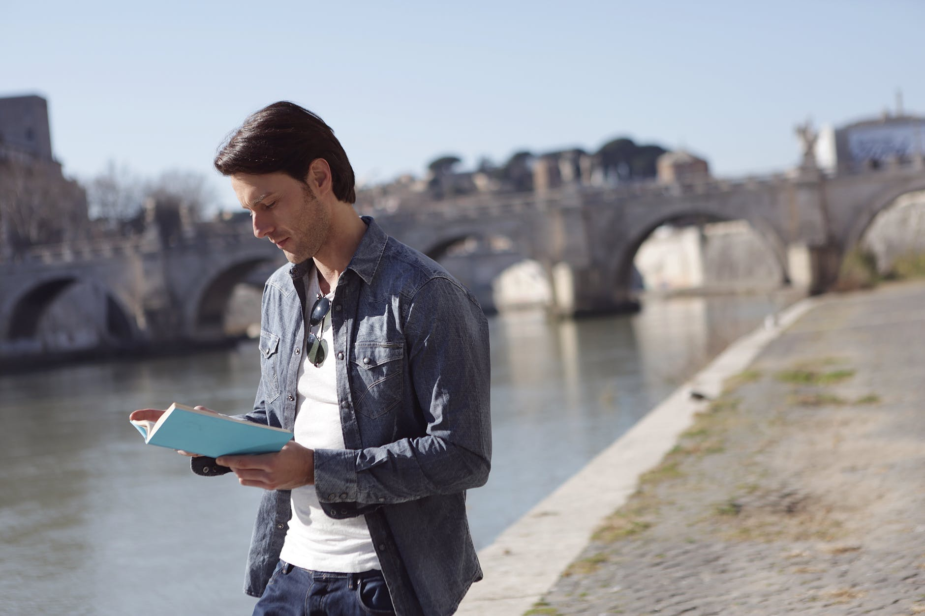 young man in denim jacket is reading a book near river side